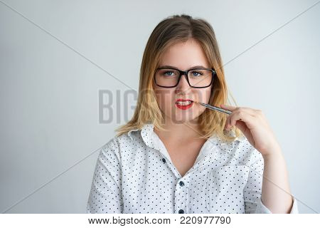 Introspective sexy business lady holding pen near face and looking at camera. Pensive confident young woman in eyeglasses thinking of business development. Teacher concept