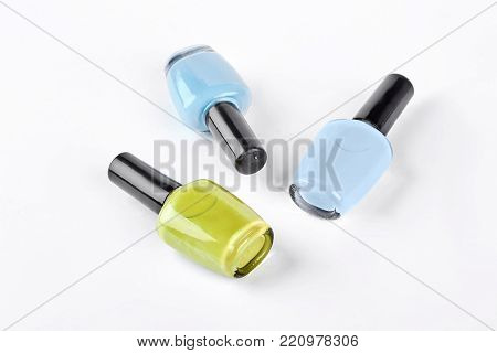 Three multicolored nail polish. Blue, light blue and yellow nail varnish isolated on white background. poster