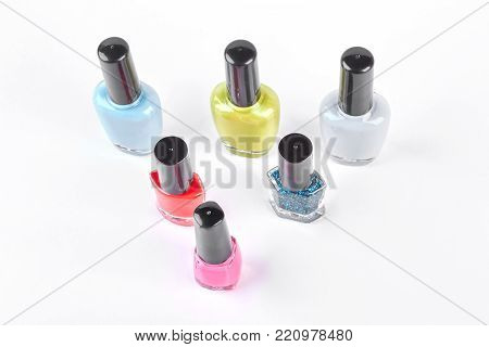 Nail polish collection, top view. Six bottles with colored nail varnish isolated on white background. High quality nail polish for manicure making.