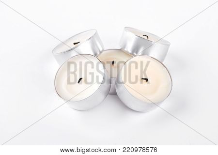 Wax candles on white background. Many small candles in circle metal base with burned wick, isolated on white background.