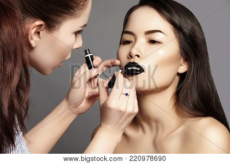 Makeup Artist Preparing Beautiful Woman before Fashion Shooting. Girl applying Lips Make-up, Asian Model with clean fresh skin
