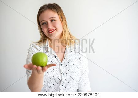 Positive beautiful young woman leading healthy lifestyle showing green apple. Cheerful confident lady eating apple for dental health. Diet concept
