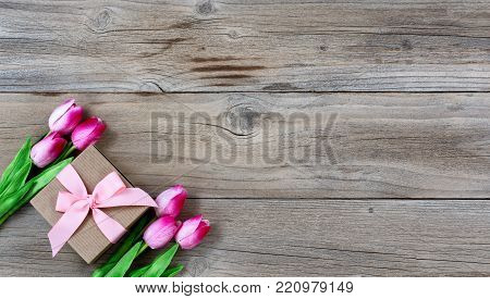 Gift box with pink tulips on rustic wooden boards for Mothers day Background