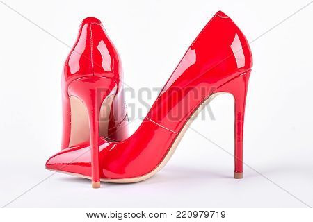 Classic red stilettos on white background. Pair of red stiletto shoes isolated on white background. Female elegant footwear.