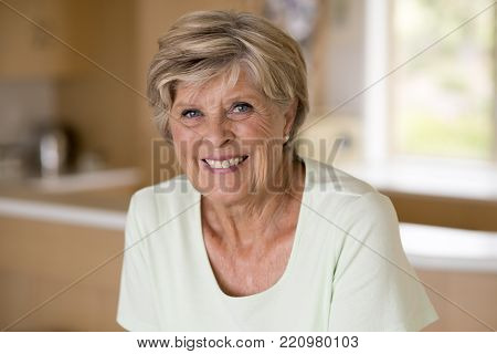 beautiful portrait of pretty and sweet senior mature woman in middle age around 70 years old smiling happy and friendly at home kitchen in aging and lifestyle concept