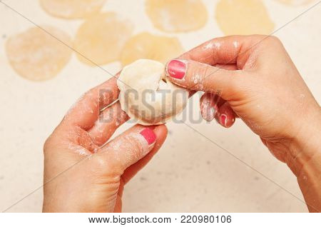 close-up, hands of chef who prepares dumplings from dough