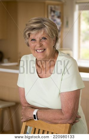 beautiful portrait of pretty and sweet senior mature woman in middle age around 70 years old smiling happy and friendly at home kitchen in aging and lifestyle concept,