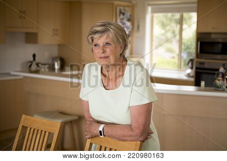 beautiful portrait of pretty and sweet senior mature woman in middle age around 70 years old smiling happy looking away thoughtful and satisfied at home kitchen in aging and lifestyle concept