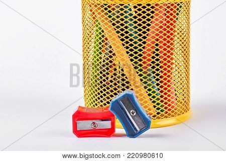 Red and blue pencils sharpeners. Yellow metal basket with pencila, two pencils sharpeners on white background.