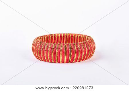 Red and gold striped bracelet. Woman fashion bracelet isolated on white background. Female stylish accessory.