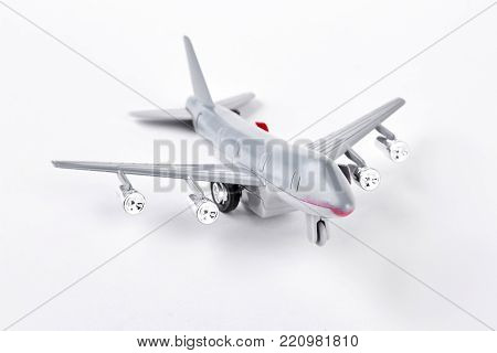 Grey toy air plane on white background. Plastic toy jet plane isolated on white background. Photo of toy air transport.