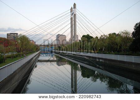 A bridge in Kiba park in Tomioka district of Tokyo reflected in Sumida river