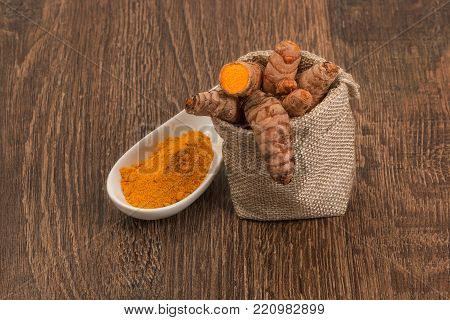Raw turmeric root in burlap sack on wooden surface