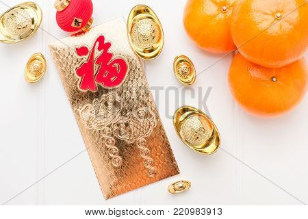 Top view Chinese New year golden envelope packet ( ang pow ) with gold ingots and tangerine on white wood table top,Chinese Language on envelop mean Happiness and on ingot mean Wealthy