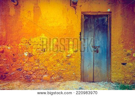 Stylish cracked vintage colorful wall in yellow orange shades with royal blue wooden door. Ideal background for retro style illustrations and collages. Grunge style. Artistic retouching. poster