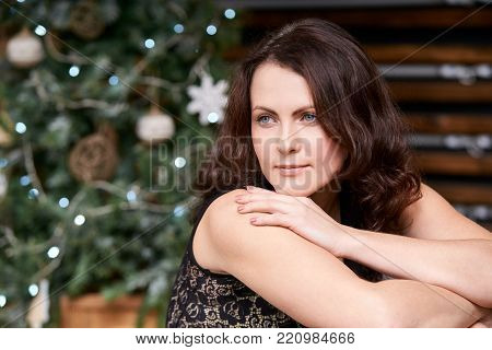 Young beautiful girl. Blurred background. Christmas tree