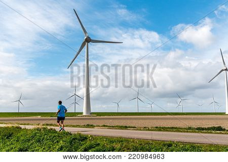 Large view on th runner on the field with windmills