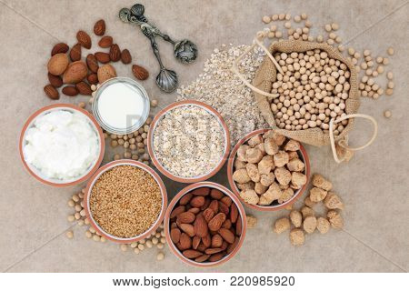 Vegan health food with nuts, seeds, soy beans, oats, soya milk, chunks and yoghurt. Foods high in fibre, antioxidants, anthocyanins, vitamins and minerals. Top view on natural hemp paper background.