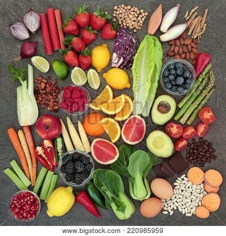 Healthy diet food concept with fresh fruit, vegetables, pulses, nuts, herbs, coffee and dark chocolate. Super foods high in antioxidants, anthocyanins, fibre and vitamins. Top view.