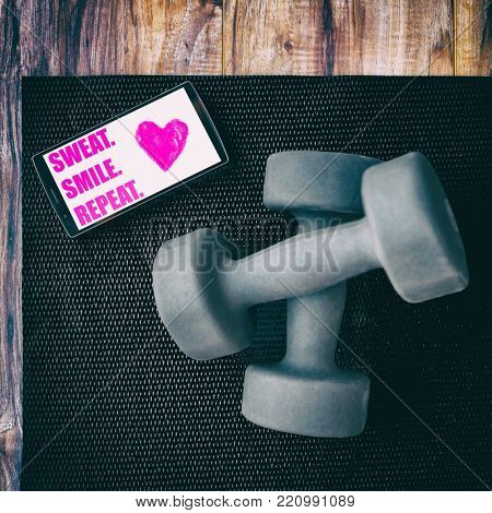 Gym fitness motivation quote SWEAT SMILE REPEAT photo for instagram social media. Positive inspirational quotes to motivate to exercise written on phone screen on exercise mat with dumbbells weights.