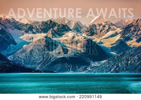 ADVENTURE AWAITS travel concept motivational quote written on nature landscape of Alaska mountain range in the wilderness. Inspirational quotes for the outdoors, go travel and discover.