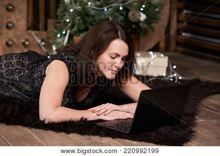Businesswoman. Computer work. Christmas tree. Beautiful girl
