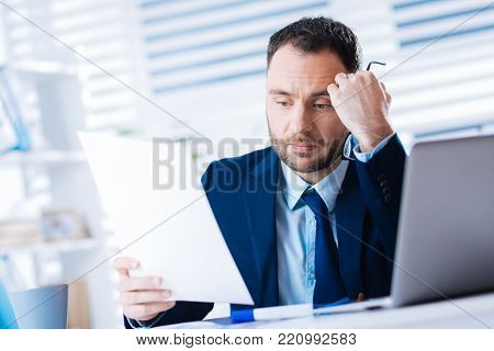 Bad news. Calm unhappy young worker of a big company sitting alone in his office and looking upset while reading unsatisfying documents