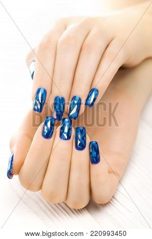 beautiful blue manicure on the white wooden table.