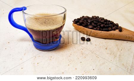 soft focus of a cup of energetic drink infusion and coffee beans on a wooden spoon with a raw background. for detox and healthy concept