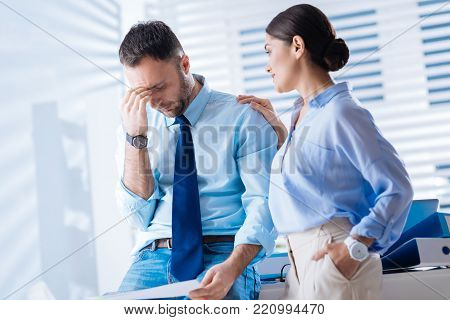 Giving up. Smart qualified tired employee standing with his hand touching the closed eyes and feeling fed up with his difficult work while a supporting kind attentive colleague standing by his side