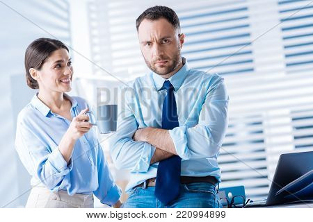 Dont worry. Positive cheerful smiling woman giving a gloomy upset man a cup of amazing hot tea and trying to cheer him up