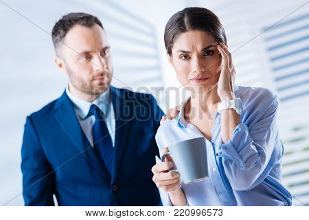 Feeling unwell. Young tired beautiful woman feeling unwell and touching her forehead while being in an office with her attentive kind colleague and holding a cup of tea