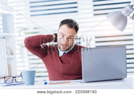 Neck aching. Young tired employee sitting in front of a laptop and doing a tiresome work while touching his neck and feeling sudden pain in it