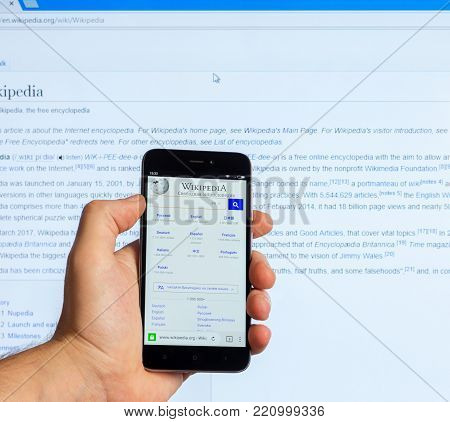 Adygea, Russia - January 5, 2018: American Public Multilingual Universal Internet Encyclopedia with free content Wikipedia on the screen of the Chinese phone Xiaomi in the male hand and on monitor