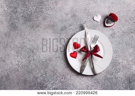 Valentines day table setting romantic dinner marry me wedding engagement ring in box with plate fork knife on grey background with copyspace. Love gift woman making proposal romantic holiday wedding