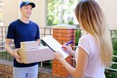 Courier Man Delivered Box to Woman to Home , Ranner Gives Pen and Documents, Girl Signs and Takes Boxes. International Manufacturer of Medical Materials Provides Courier For Purchases, Messenger For You, Courier Man of European Appearance Provides Pen and poster