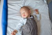 Cute little Asian 1 year old toddler baby boy child sleeping in baby cot, Peaceful kid lying on baby bed while sleeping with windows light at his face, Daytime sleep concept (shallow depth of field) poster