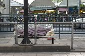 unidentified tramp man sleep in blanket cover on bench in public place in Bangkok, Thailand. poster