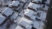 Aerial drone photo, top down, of suburban houses in Oakville, Ontario, Canada everything is white and covered with snow in the sunshine. poster