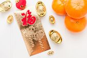 Top view Chinese New year golden envelope packet ( ang pow ) with gold ingots and tangerine on white wood table top,Chinese Language on envelop mean Happiness and on ingot mean Wealthy poster