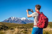 Tourist hiker man taking picture with phone of mountains in New Zealand during hike on Tongariro Alpine crossing track in New Zealand, NZ. Travel tramping lifestyle. poster