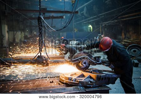 Grinding In A Steel Factory. Worker With A Big Saw Cutting Metal.