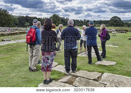 11 August 2018: Northumberland, Uk - Visitors Listening To A Guide On A Tour At Chesters Roman Fort,