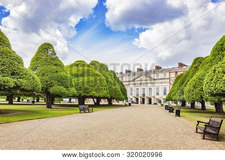 9 June 2019: Hampton Court, Richmond Uk - The East Front Of The Palace, Seen Beyond An Avenue Of Yew