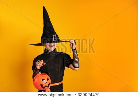 Halloween Celebration. Little Girl In A Witch Costume Holds A Pumpkin Jack Bucket On A Yellow Backgr