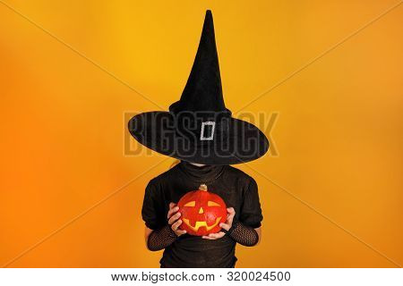 Halloween Celebration. Little Girl In A Witch Costume Holds A Pumpkin Jack On A Yellow Background. T