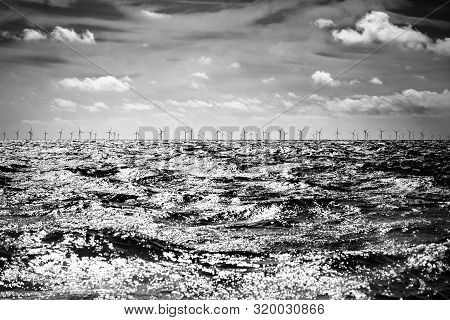 Offshore Wind Farm On Horizon With Cloud And Waves