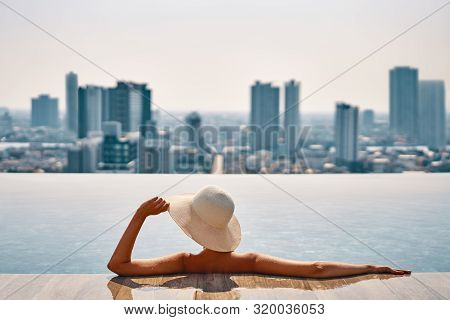 Back View Of Young Woman In Hat Relaxing In Swimming Pool On The Roof Top Of Hotel And Enjoy Citysca