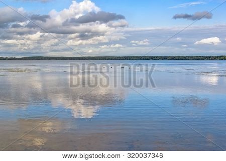 Picturesque Landscape With A Lake And Reflection In The Water Of A Blue Sky And White Clouds On A Su