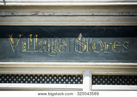 Weathered Village Stores Sign Above Local Business In English Village